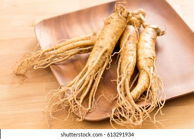 Fresh ginseng root over wooden background