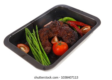 fresh glazed baked big beef meat rib chunk under sweet sauce with tomatoes hot chili pepper pink peppercorn and asparagus in black tray isolated on white background