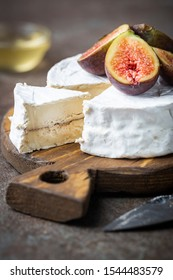 Fresh goat brie cheese with white mold on cutting board, wooden background
