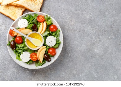 Fresh goat cheese salad with lettuce, cherry tomatoes, Apple, Kalamata olives and a dressing of olive oil and toasted bread. Copy space top view