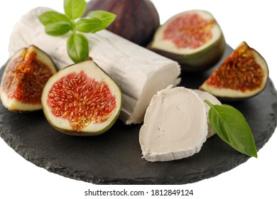 Fresh goat cheese and sweet figs on clack stone board isolated on white - healthy diet. Selective focus