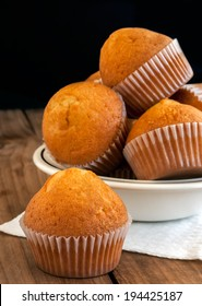 Fresh golden muffins on a wooden table