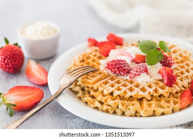 Fresh golden waffles with chopped strawberries and whipped cream.  White plate, gray background and a piece of white fabric next to the plate. There are whole and halfed strawberries on the table.