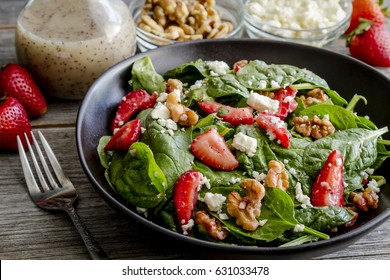 Fresh gourmet organic strawberry spinach salad with feta cheese, walnuts and poppy seed dressing sitting in black bowl surrounded by salad ingredients