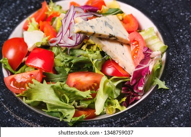 Fresh gourmet salad with gorgonzola cheese. Healthy eating concept. Green salad with tomatoes and blue cheese