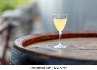 Fresh grape juice in a glass on a wood barrel