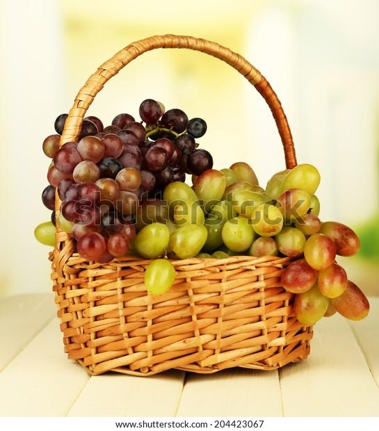Fresh grape on wicker mat on bright background