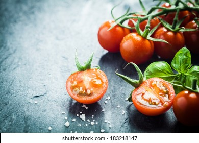 Fresh grape tomatoes with basil and coarse salt for use as cooking ingredients with a halved tomato in the foreground with copyspace