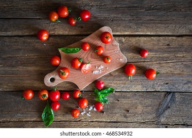 Fresh grape tomatoes with basil and coarse salt for use as cooking ingredients with a halved tomato in the foreground on kitchen board