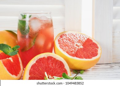 Fresh grapefruits and glass of grapefruit juice with ice and mint on rustic white wooden table opposite the blinds with copy space.  Close-up.