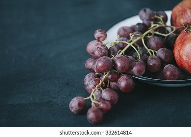 fresh grapes and pomegranate in old vintage plate, on dark blue colored table