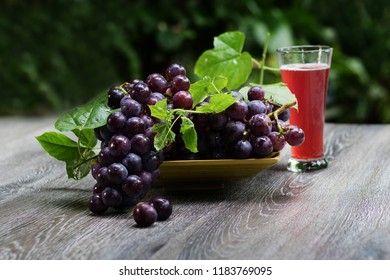 Fresh grapes and purple grape juice on the table./Bunch of Grapes with water droplets