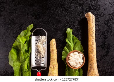 Fresh and grated horseradish in wooden bowl with grater, leaves and roots from above.