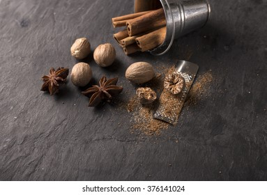 fresh grated nutmegs and whole ones over black background