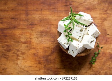 Fresh Greek Feta Cheese. Healthy ingredient for cooking salad. Crumbled Goat feta cheese on cutting board.