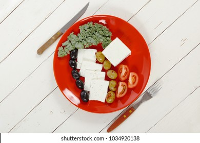 fresh greek feta cheese sandwich on red plate with hot green olives and black, goat cheese cube, tomatoes kale over retro table