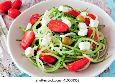 Fresh Greek Salad with cucumber noodles close up on vintage plate