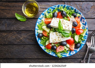 Fresh Greek salad of cucumber, tomato, sweet pepper, red onion, feta cheese and olives with olive oil. Healthy food, top view