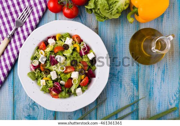 Fresh Greek salad on a plate. blue wooden board. Top view.