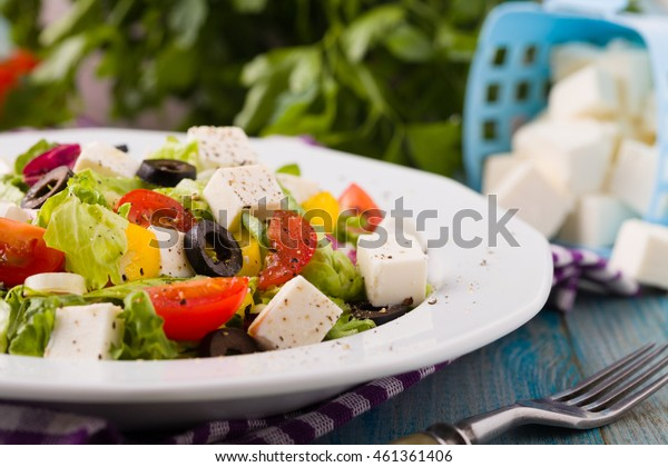 Fresh Greek salad on a plate. blue wooden board.