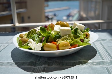 Fresh Greek salad on a white plate in the sun, Glyfada, Athens