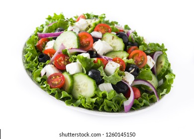 Fresh Greek salad in Plate with black olive,tomato,feta cheese, cucumber and onion isolated on white background. Close up