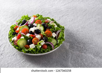 Fresh Greek salad in Plate with black olive,tomato,feta cheese, cucumber and onion on gray background. Copyspace