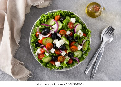 Fresh Greek salad in Plate with black olive,tomato,feta cheese, cucumber and onion on gray background. Top view