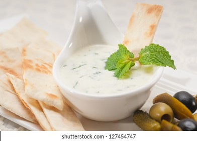 fresh Greek Tzatziki yogurt dip and pita bread and pickels