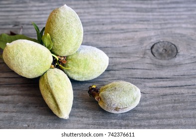 Fresh green almond tree branch with almond nuts and leaves on old wooden background.Healthy snack or diet concept. Selective focus.