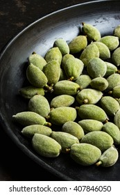 Fresh green almonds on a black wooden plate