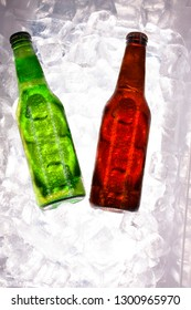 Fresh green and amber beers in a cold cooler ready for consumption surrounded by ice cubes ready for the picnic in Mexico
