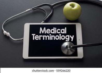 Frische grüne Apfel und Stethoskop mit dem Wort Medical Terminology auf digitalen Tablets. Medizinisches Konzept.