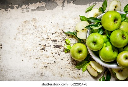 Fresh green apples in a dish on a rustic background.  Free space for text . Top view
