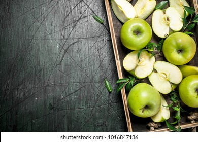 Fresh green apples on a wooden tray. On a rustic background.