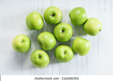 fresh green apples on wooden white background, top view