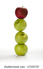 Fresh green apples stacked on top of one another with a red apple on top