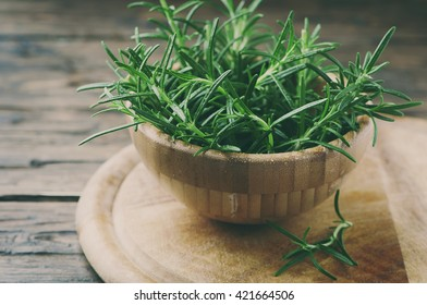Fresh green aromatic rosemary on the wooden table, selective focus and toned image
