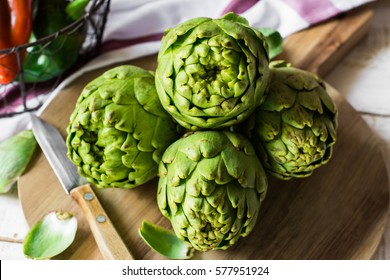 Fresh green artichokes on cutting board top view with peeled off leaves, Italian sweet peppers in basket on kitchen table, linen towel