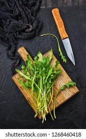 Fresh green arugula on wooden board. Arugula rucola for salad.