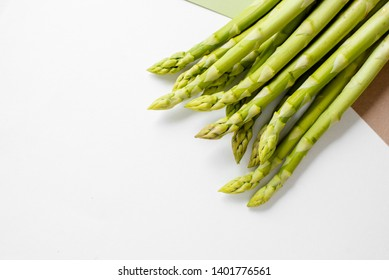 Fresh green asparagus on a bright beautiful trendy background. Asparagus sprouts close up. Top view. Healthy and organic food. Raw products, fresh vegetables