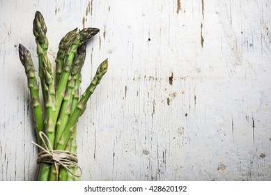Fresh green asparagus on rustic white table background. Healthy eating recipes. Vegetarian and vegan cuisine. Organic food ingredients.