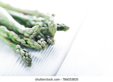 Fresh green asparagus on white wooden board, macro and shallow depth
