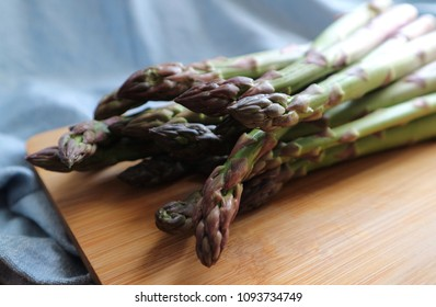 Fresh green asparagus on a wooden board with blue cloth. Raw uncooked asparagus. Side view. Selective focus