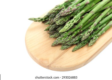 Fresh green asparagus on a wooden cutting board isolated on white background.