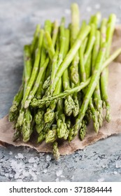 Fresh green asparagus with sea salt on a craft piece of paper and and on a marble table