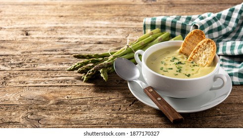 Fresh green asparagus soup in bowl on wooden table.Copy space