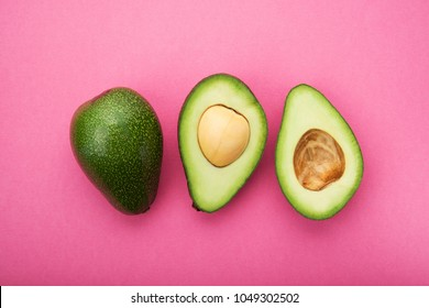 Fresh green avocado on a pink pastel background. healthy diet concept. top view