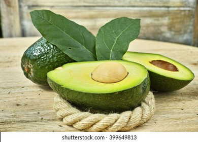 Fresh green avocado on wooden background, copy space