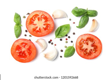 Fresh green basil leaves, tomatoes and garlic on white background, top view